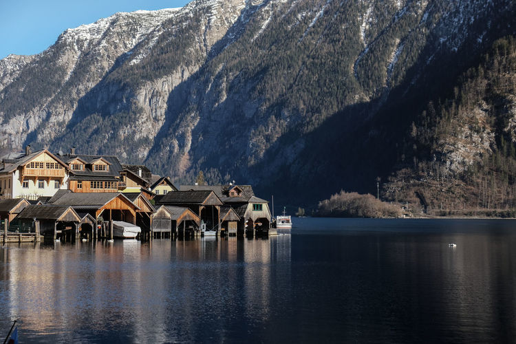 Houses of hallstatt by lake and mountains against sky