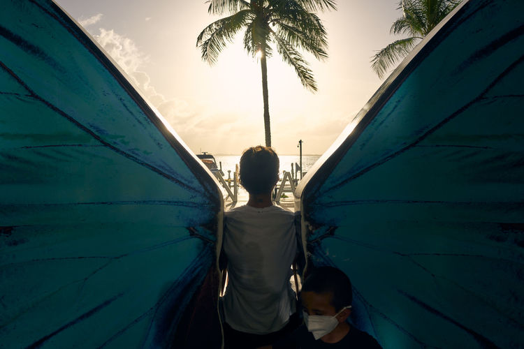 Rear view of woman and boy standing by palm trees against sky