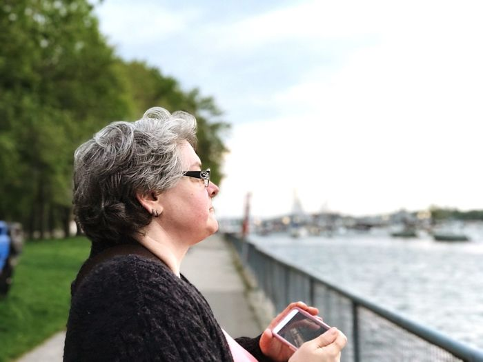 Side View Of Mature Woman Holding Mobile Phone By River In City