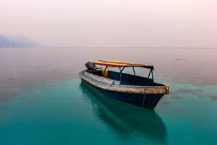 Boat moored on sea against sky