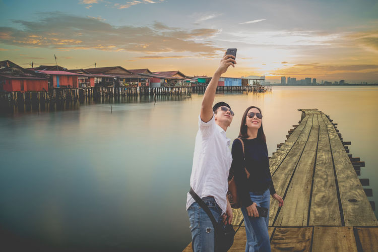 Man taking selfie with woman while standing on pier against sky during sunset