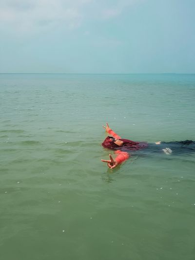 Person in sea against sky