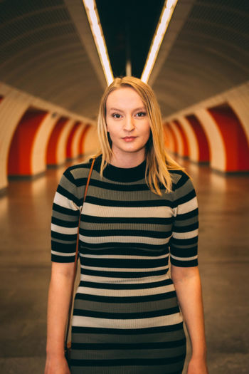 Portrait Of Young Woman Standing In Illuminated Tunnel