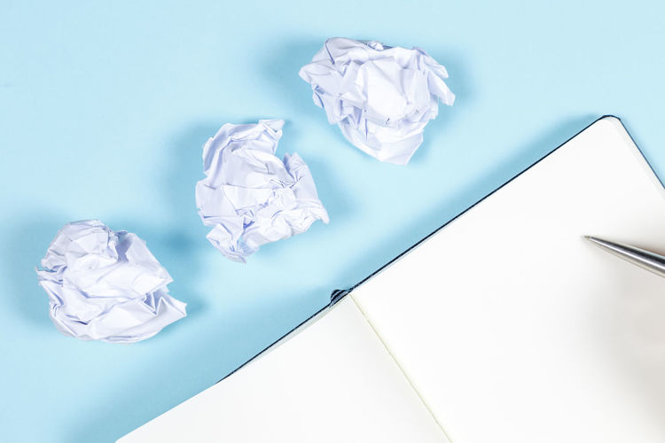 Crumpled Paper Crumpled Paper Indoors  Crumpled Paper Ball No People Studio Shot Negative Emotion Copy Space Close-up Blue High Angle View Frustration Emotion White Color Still Life Table Garbage Group Of Objects Blue Background Clean
