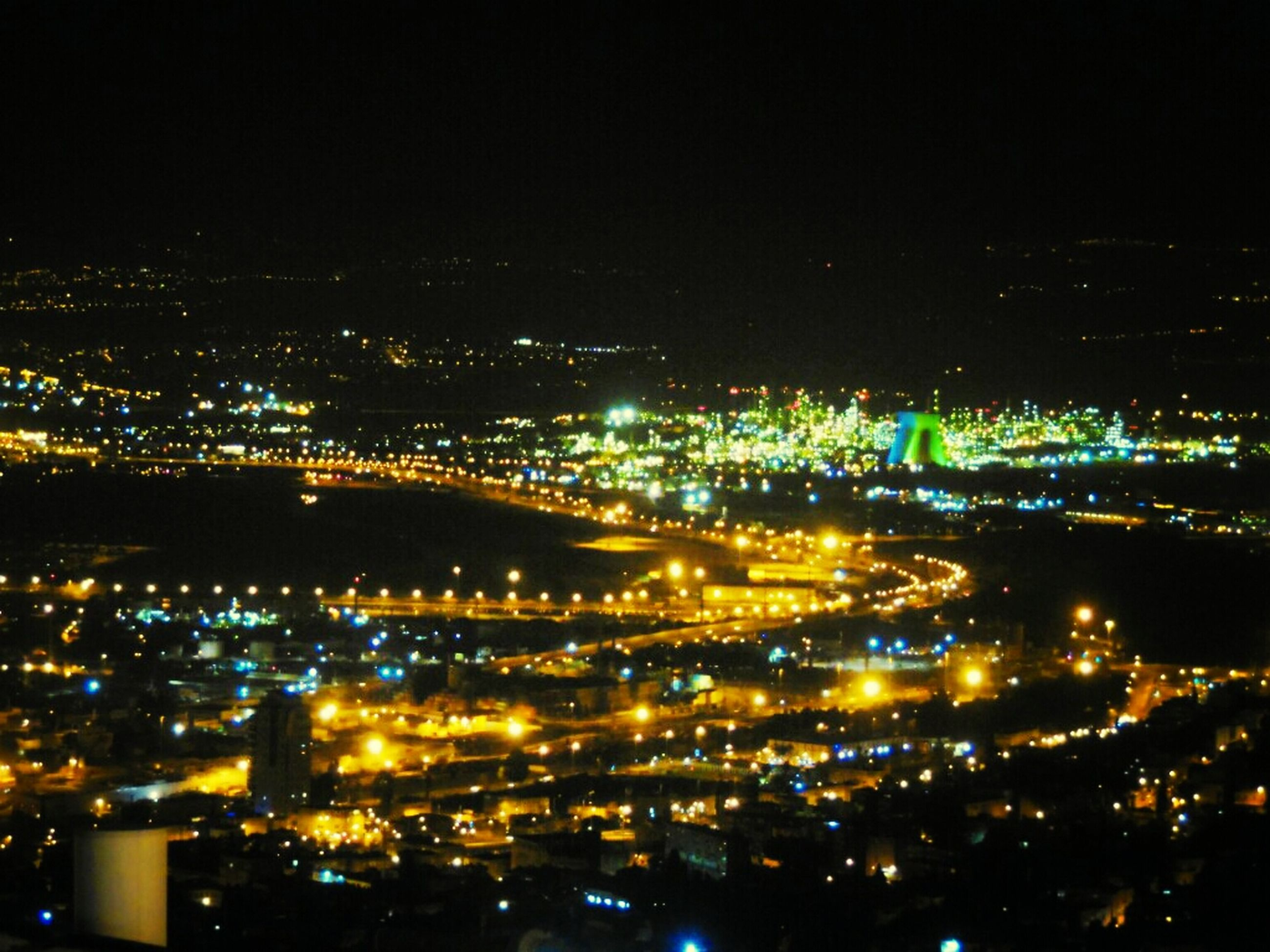 illuminated, night, cityscape, city, high angle view, aerial view, crowded, building exterior, architecture, built structure, city life, residential district, sky, residential building, outdoors, no people, road, residential structure, elevated view, landscape