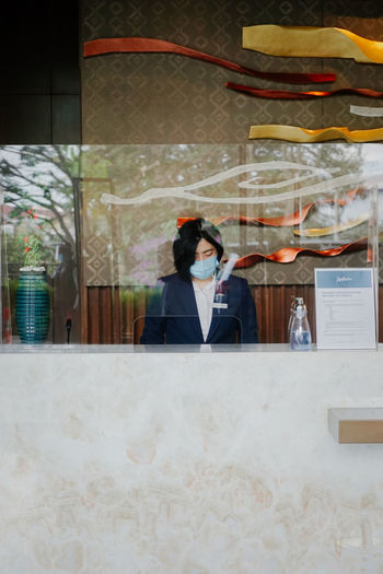 Receptionist wearing mask working in hotel