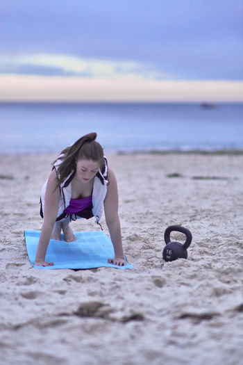 Woman Exercising At Beach Against Cloudy Sky