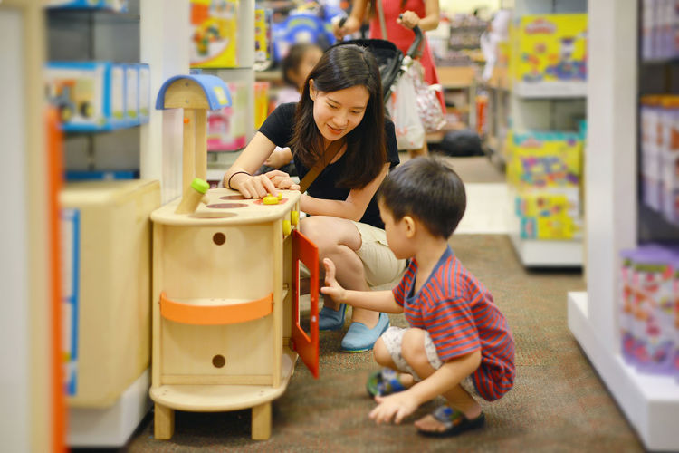 Boy With Mother Looking At Toys In Shopping Mall