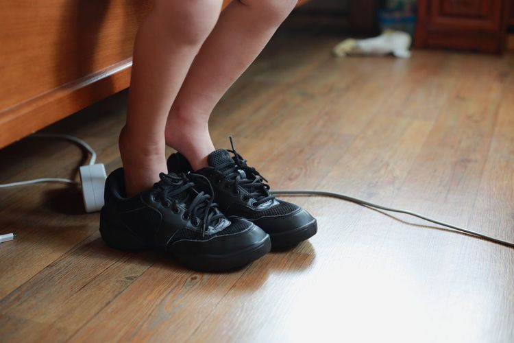 Low section of baby wearing shoes on wooden floor at home