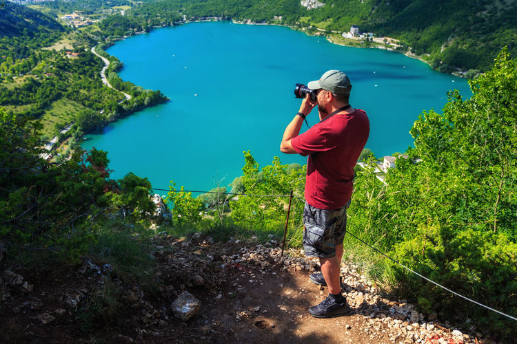 Full length of man photographing in lake