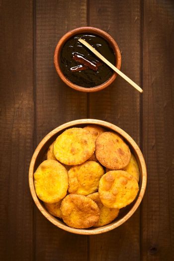 Chilean Sopaipilla fried pastry made with mashed pumpkin in the dough, served with Chancaca sweet sauce, photographed on wood with natural light Breakfast Chile Chilean  Dessert Homemade Homemade Food Latin America Snack South American Food Chancaca Chilean Food Deep Fried  Food Food And Drink Fried Latin American Overhead View Pastry Pumpkin Sauce Sopaipilla Nortena Sopaipillas Sweet Top View Vertical