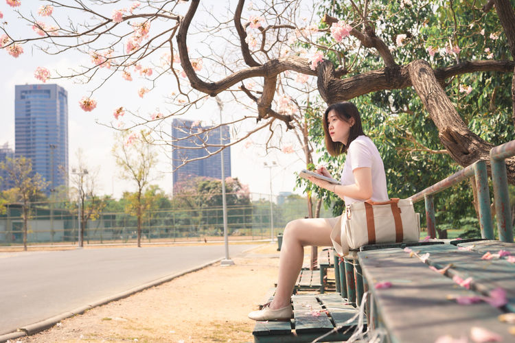 Woman sitting in park by city
