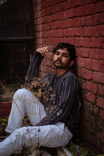 Portrait of young man sitting against brick wall