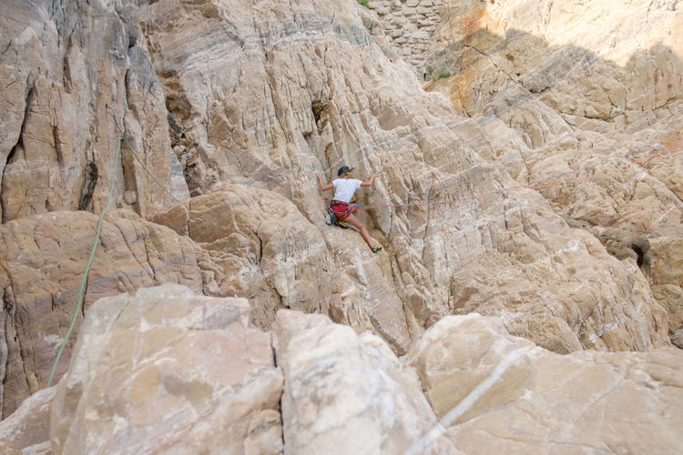 Rear view of woman climbing on rock