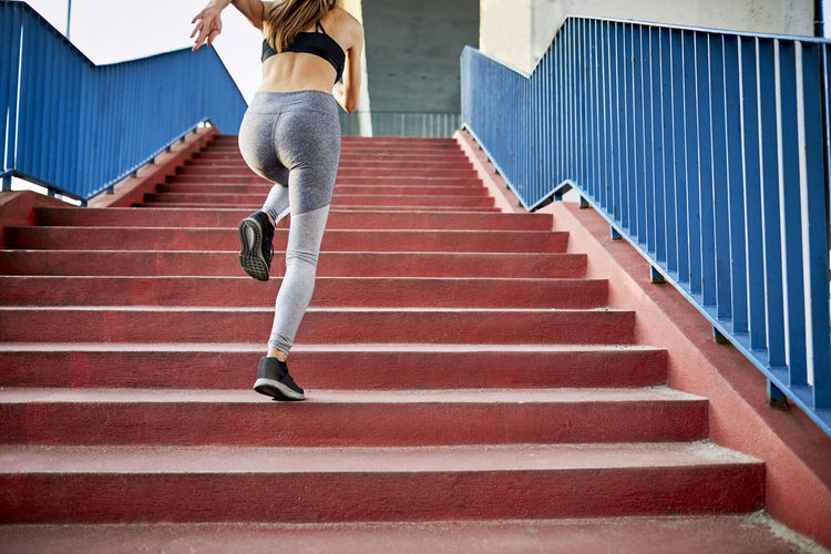 Rear view of woman running on staircase