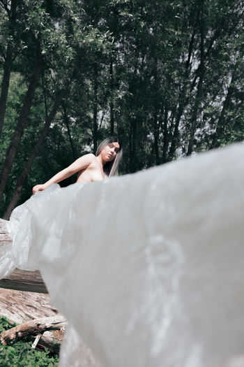 Naked woman holding polythene standing in forest