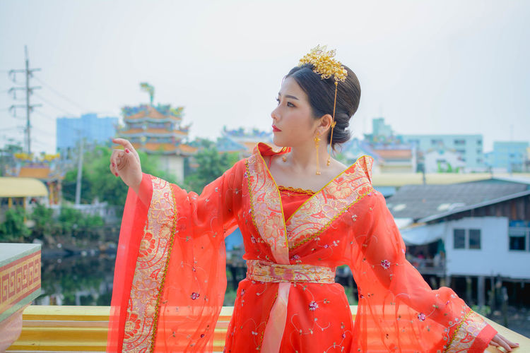 Young woman in traditional clothing standing at temple