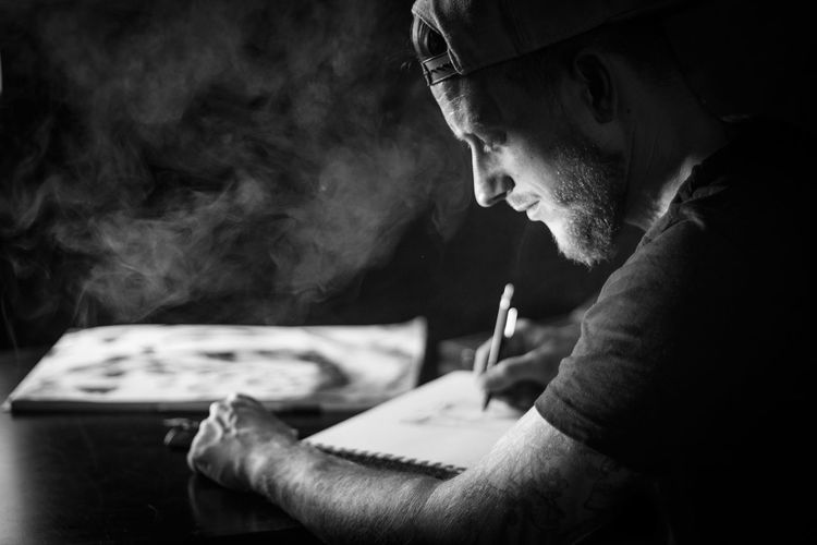Side View Of Man Making Drawing On Paper Against Black Background
