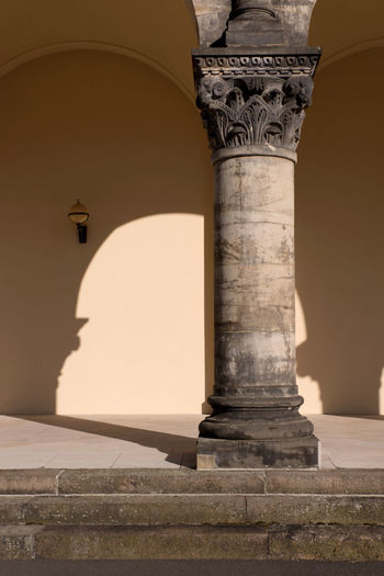 Close-up of bottom single old stone column and blank wall and sunlight with arch shadows - heritage and tradition- copy space Authority Tradition Arches Architectural Column Blank Wall Carved Stone Column Corinthian Columns Culture Europe European Heritage Generic Architecture Heritage History Light And Shadow Neoclassical Neutral Background No People Outdoors Sandstone Stone Stone Texture