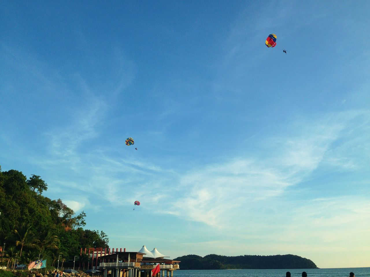 mid-air, adventure, parachute, flying, freedom, parasailing, sky, leisure activity, extreme sports, beach, outdoors, nature, paragliding, blue, low angle view, day, vacations, real people, lifestyles, sport, hot air balloon, tree, one person, people