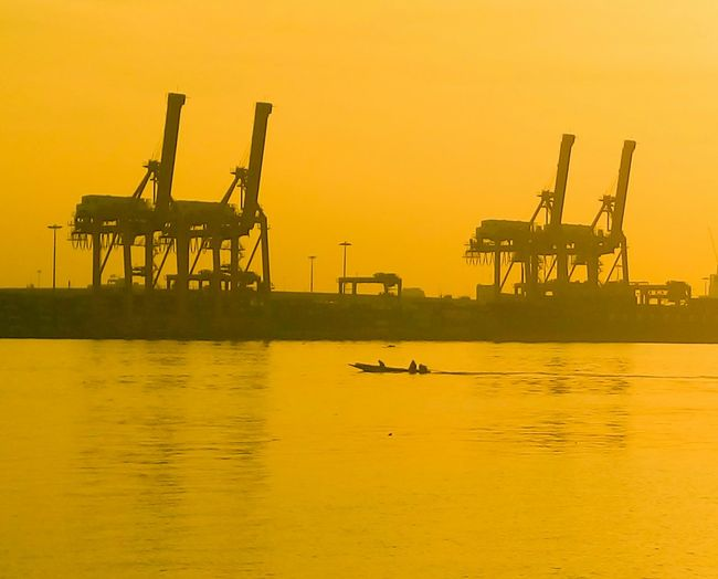 Silhouette cranes at riverbank of chao phraya at sunset