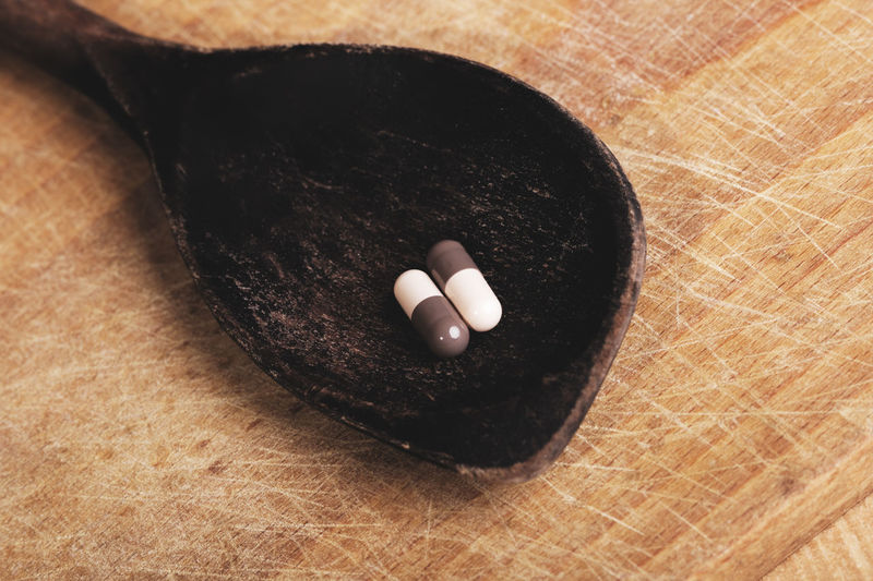Tablets pill on wooden dark spoon concept on old board with scratches background Pill Pills Tablets Vitamins Antibiotic Antiseptic Healthcare And Medicine Capsule Vitamin Capsules And Pills PainKiller Painkillers Pharmaceutical Medical Medicament Addiction Addict Close-up Still Life Brown Spoon Wooden Texture Wooden Spoon Wooden Table Illness