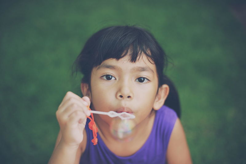 High angle portrait of cute girl blowing bubble