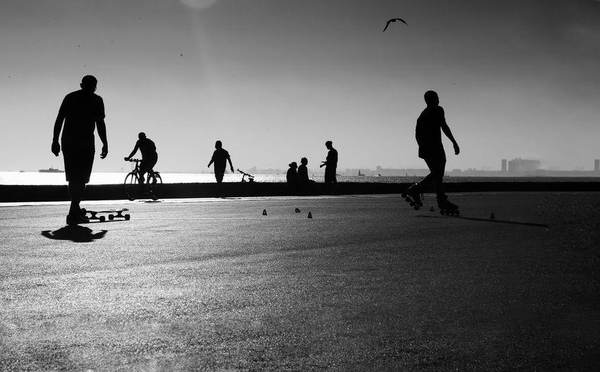 Silhouette people skateboarding on road against sky