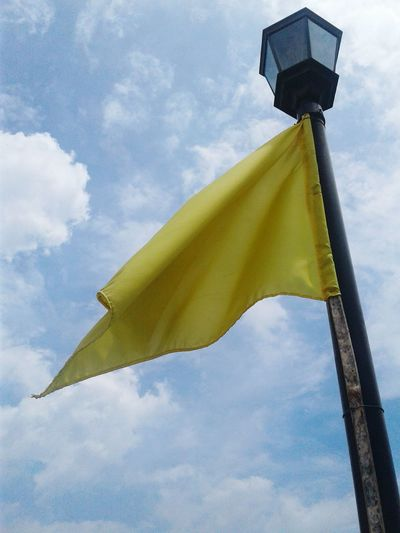 Low Angle View Yellow Sky Cloud Cloud - Sky Flying Blue Flag Pole Outdoors Day Fluttering Sunshade No People Paint The Town Yellow