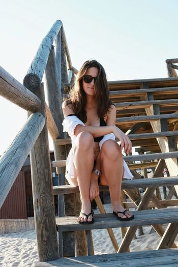 Portrait Of Young Woman Sitting On Steps At Beach