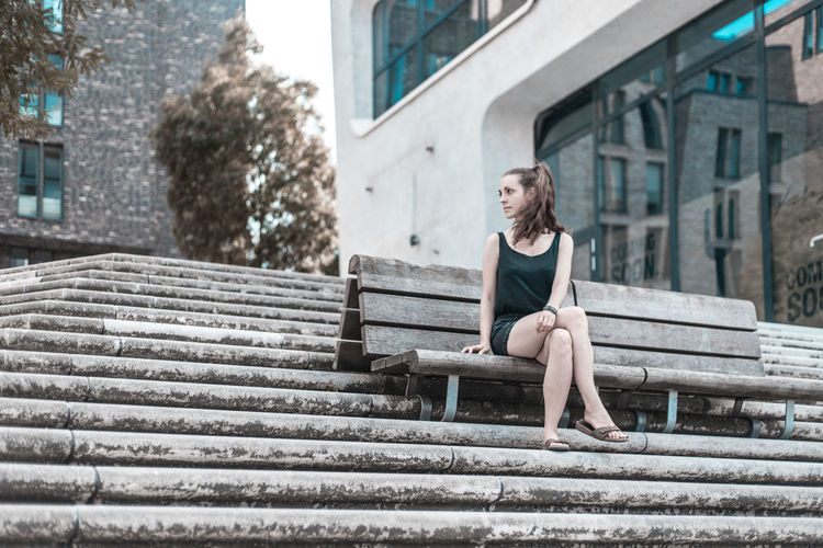 Full Length Of Young Woman Looking Away While Sitting On Bench In City