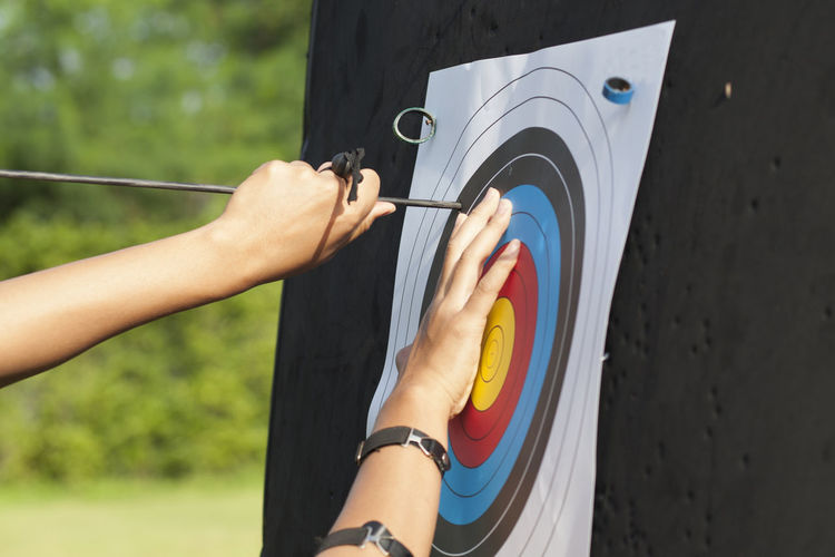 Cropped Hand Of Woman Removing Arrow From Sports Target