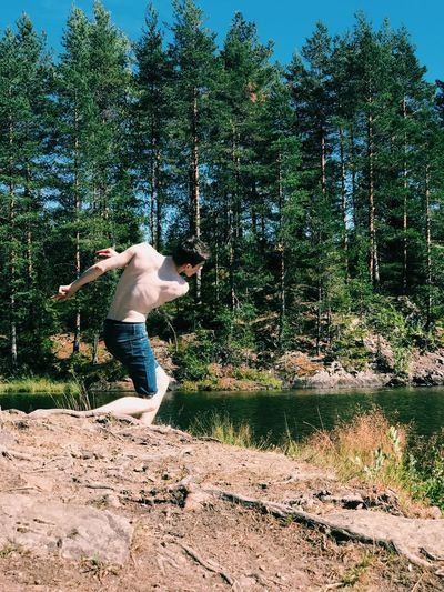 Shirtless young man skimming stones in lake a forest