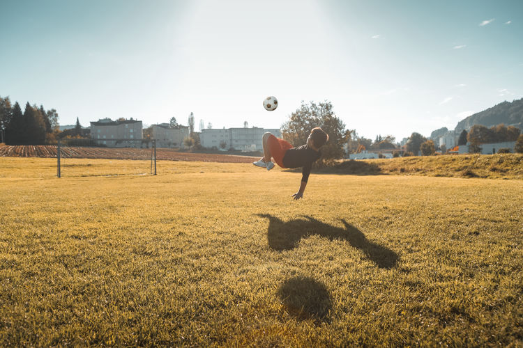 Boy playing soccer on land during sunny day