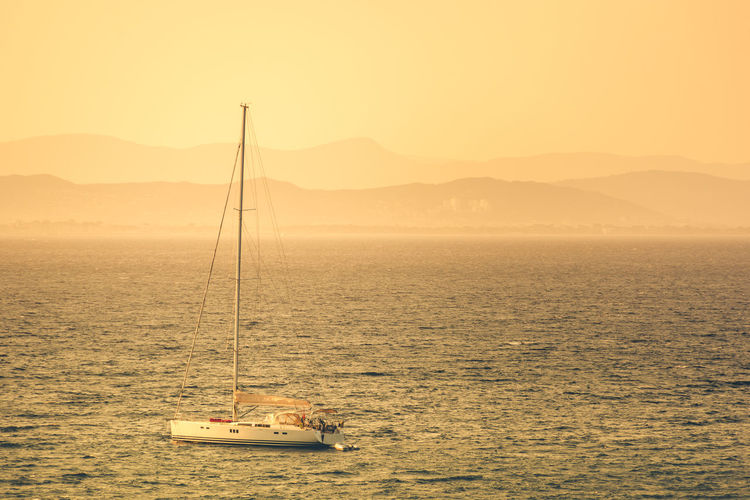 Mediterranean feel, sunset view from the island of Porquerolles near Hyeres, France. Beach Beauty In Nature Côte D'Azur French Coastline Mediterranean Feel Mountain Mountain Range Nautical Vessel Scenics Sea Sunlight Sunset Tranquil Scene Tranquility Water Yacht In The Foreground Yachting Yachtlife Yellow Sunset Light Betterlandscapes Light And Shadow