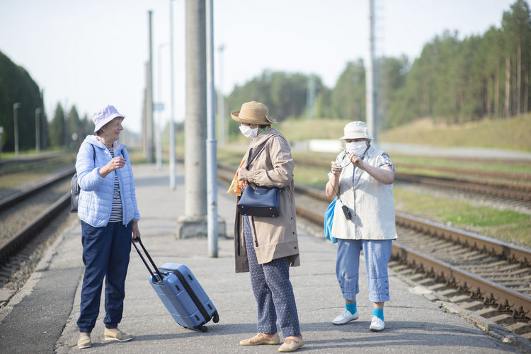 Three old senior women on  platform waiting for the train and wearing a face mask during a pandemic