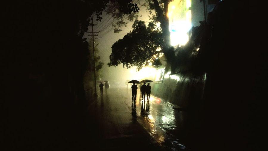 Silhouette people walking on sidewalk in city