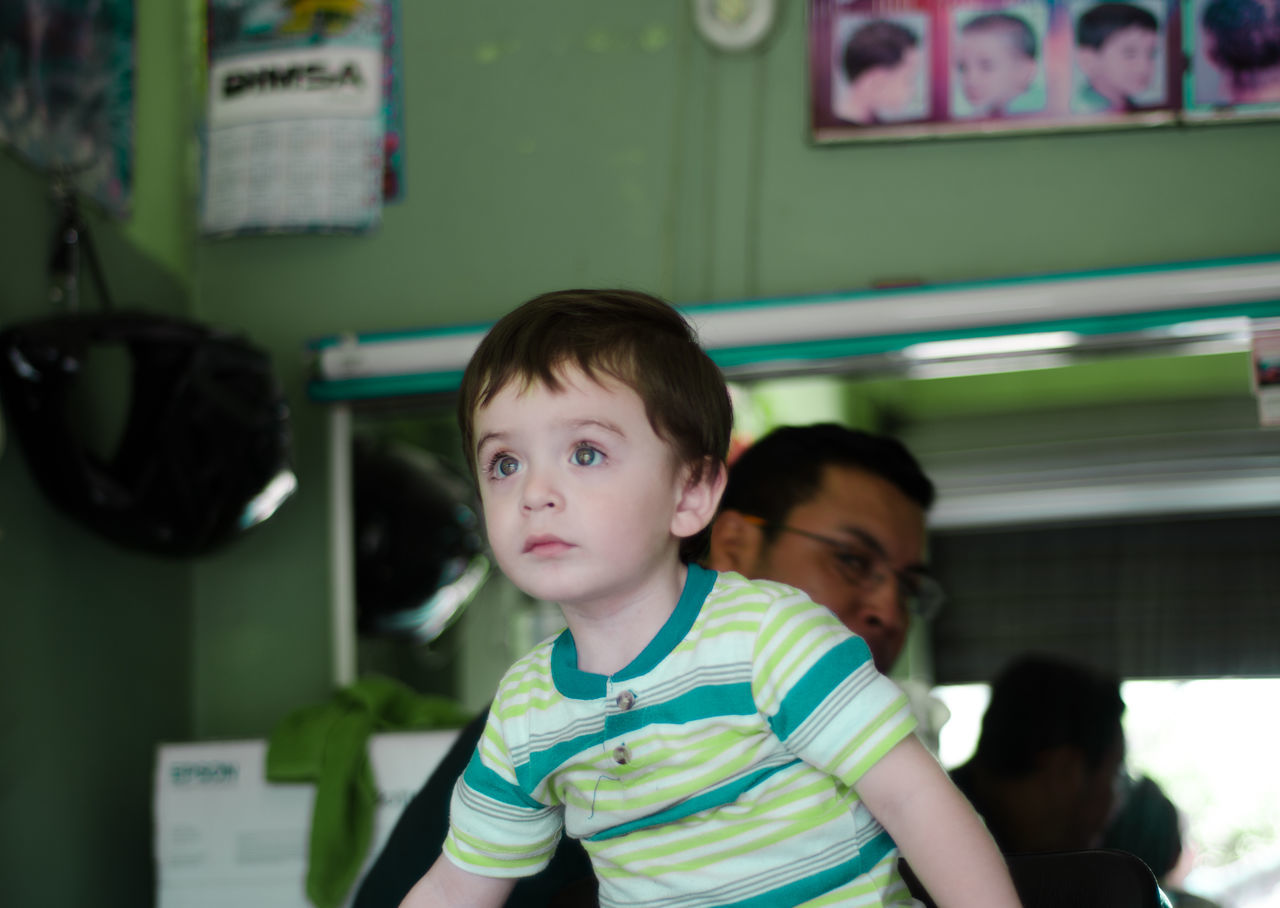 Low Angle View Of Cute Boy In Barber Shop