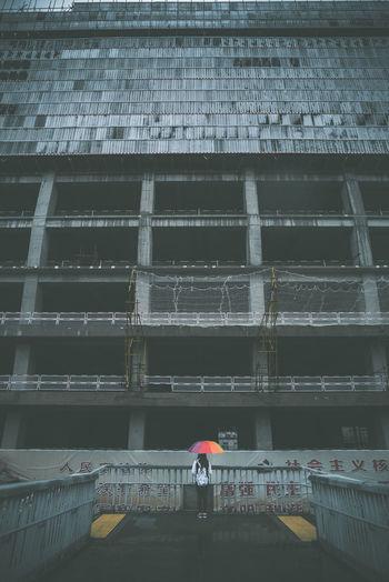 Full length rear view of wet walking on building