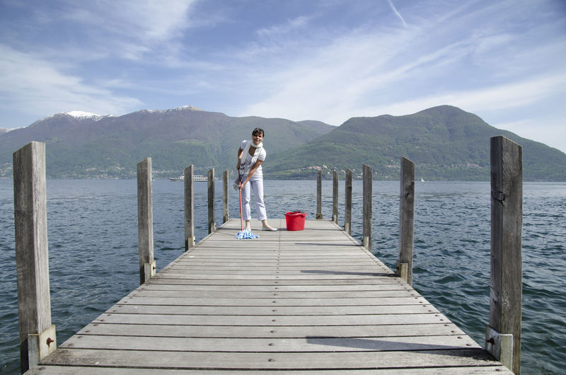 Woman Cleaning a Pier on Alpine Lake Maggiore with Mountain in Ticino, Switzerland. Cleaning Humor Sunny Woman Beauty In Nature Bucket Day Daylight Dimishing Perspective Jetty Mops Mountain Nature One Person One Woman Only Outdoors People Pier Real People Scenics Sea Sky Standing Water Wood - Material