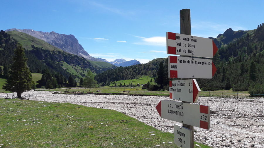Dolomites Communication Day Direction Guidance Information Information Sign Mountain Mountain Range Nature No People Non-urban Scene Non-western Script Outdoors Road Road Sign Scenics - Nature Script Sign Sky Text Western Script