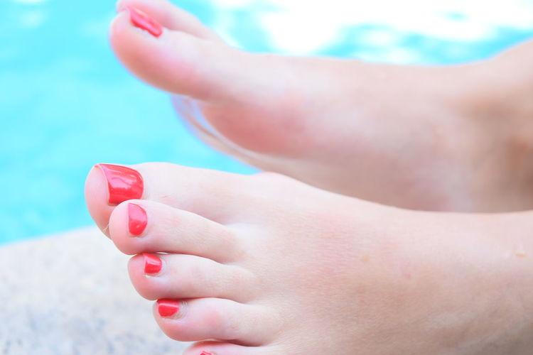 Low section of woman with red painted toenails against swimming pool