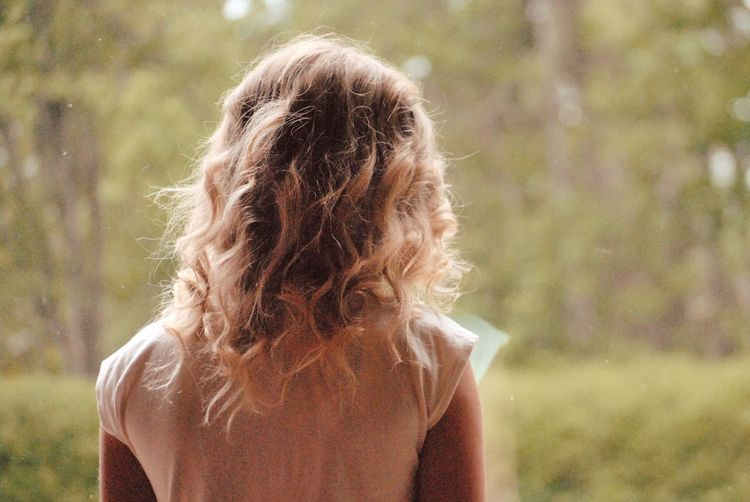 Rear view of girl with blond hair standing in forest