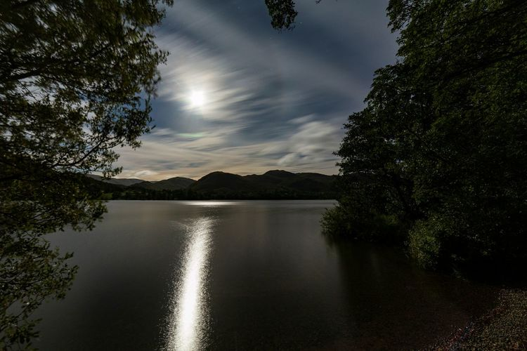 Scenic view of ullswater with the moon shining through the cloudy sky