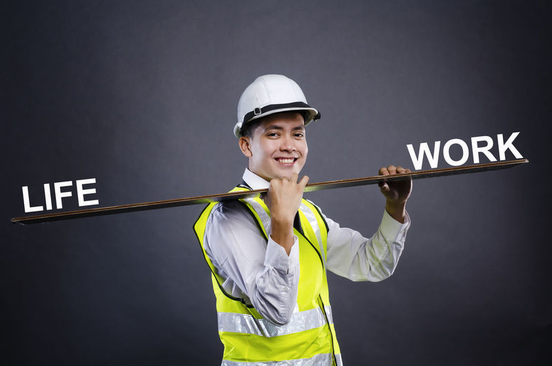 happy face young engineer or manager with white safety helmet holding wooden board. One Person Front View Young Adult Smiling Standing Portrait Text Clothing Looking At Camera Waist Up Helmet Communication Western Script Young Women Holding Headwear Lifestyles Studio Shot Indoors