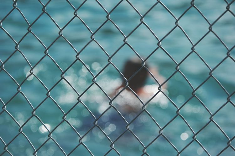 Full frame shot of chainlink fence against lake on sunny day