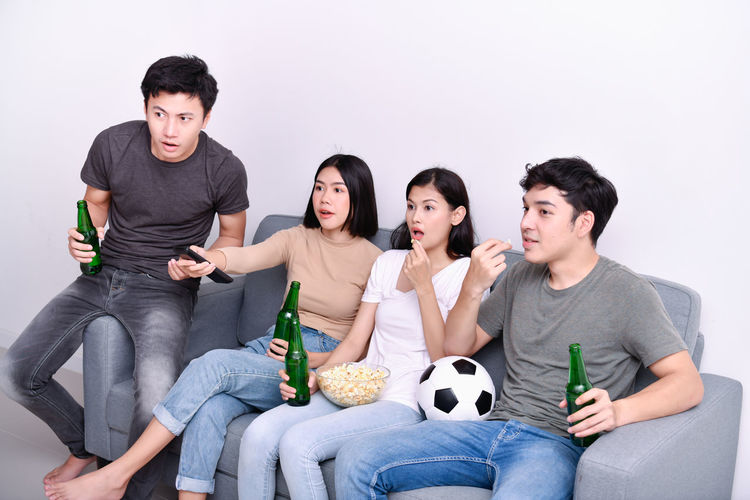 Shocked Friends Having Popcorn And Drink While Sitting On Sofa At Home