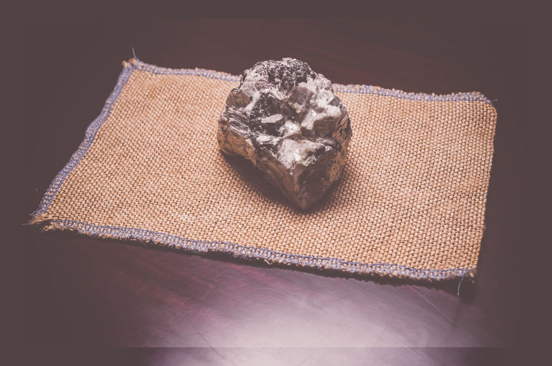 Close-up of quartz and mica schist rock on jute fabric over table