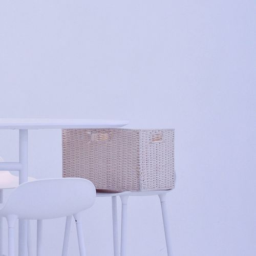 Wicker Basket On Chair Against White Background