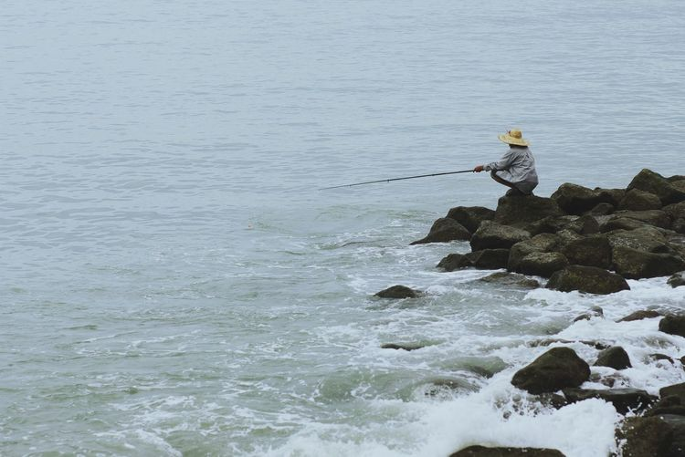 Fishing Nature Water Sea Outdoors Day Real People One Person People Fishing Fisherman Catch Of The Day Old People Waves Waves And Rocks Beauty In Nature